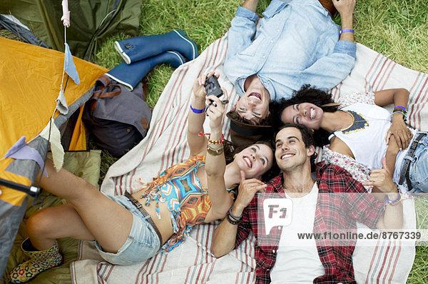 Freunde mit Selbstporträt auf Decke vor dem Zelt beim Musikfestival