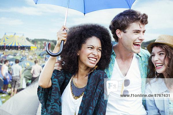 Freunde mit Schirm beim Musikfestival