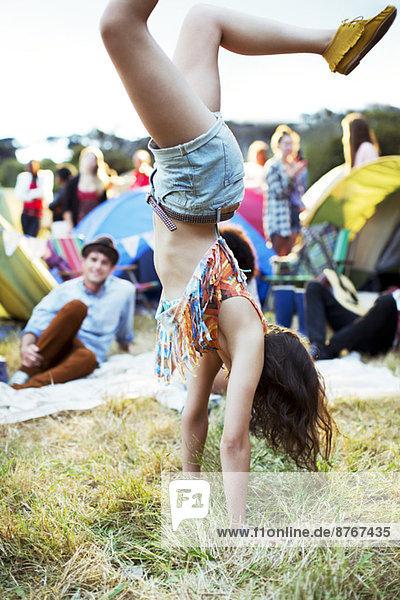Frau macht Handstand vor Zelten beim Musikfestival