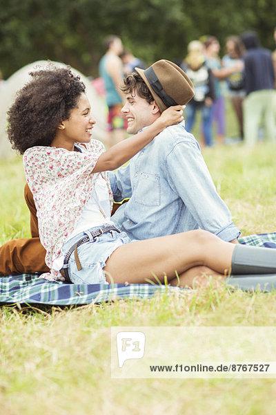 Paarumarmung auf der Decke im Gras beim Musikfestival