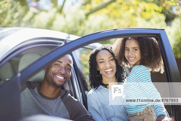 Porträt einer glücklichen Familie innerhalb und außerhalb des Autos