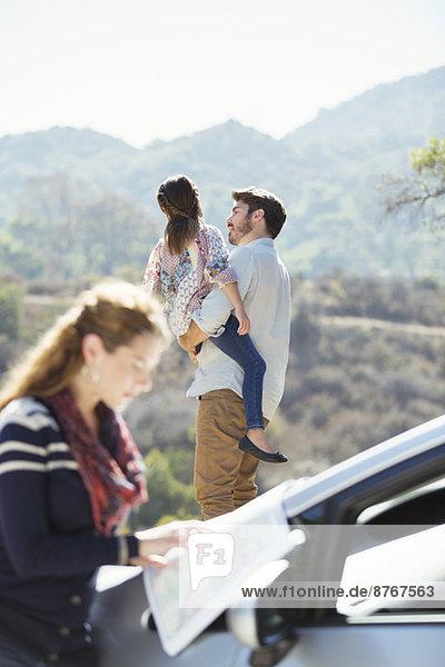 Vater hält Tochter am Straßenrand  während Frau die Karte überprüft