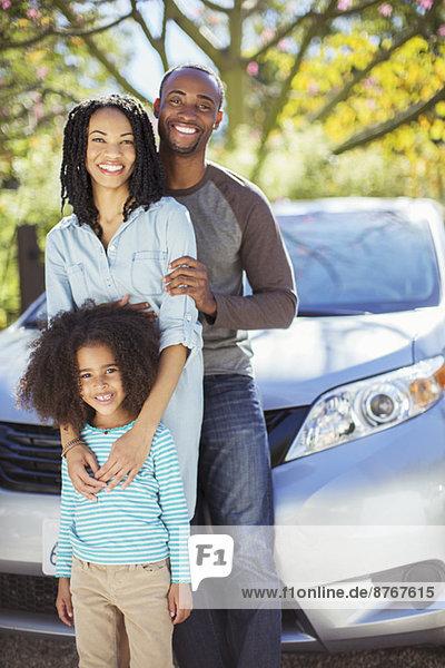 Porträt einer glücklichen Familie außerhalb des Autos