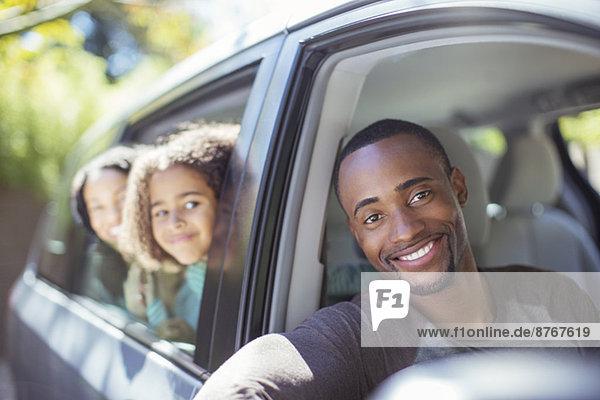 Porträt einer glücklichen Familie  die sich aus den Autoscheiben lehnt.