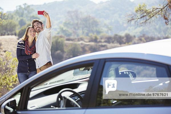 Selbstporträt eines Paares mit Handy außerhalb des Autos