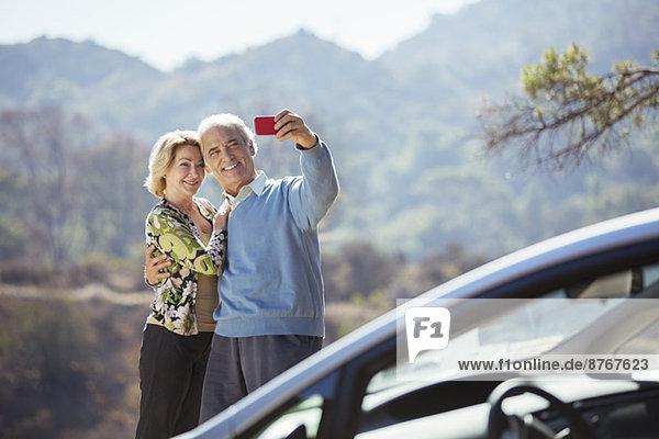 Seniorenpaar beim Selbstporträt mit Handy vor dem Auto