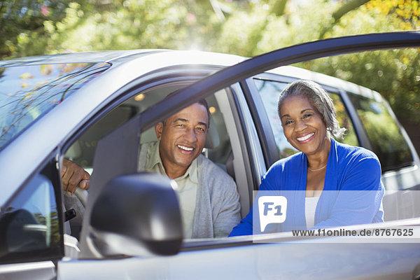 Porträt des glücklichen Paares innerhalb und außerhalb des Autos