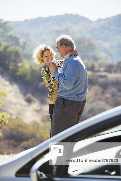 Happy senior couple dancing at roadside outside car