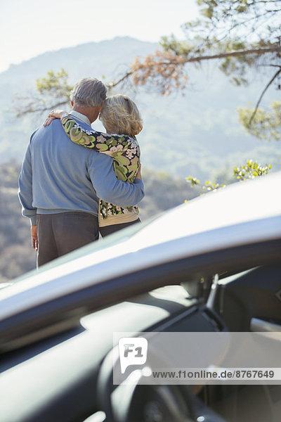 Seniorenpaar mit Blick auf die Berge außerhalb des Autos