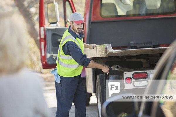 Mechaniker am Straßenrand bei der Vorbereitung zum Abschleppen des Fahrzeugs