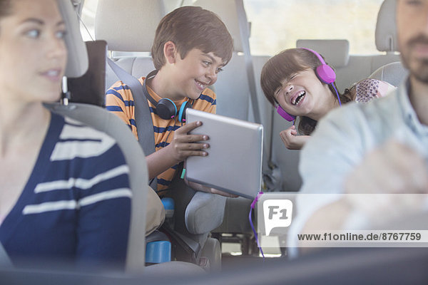 Glückliche Geschwister mit digitalem Tablett auf dem Rücksitz des Autos