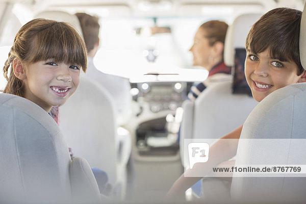 Porträt der glücklichen Geschwister auf dem Rücksitz des Autos Porträt der glücklichen Geschwister auf dem Rücksitz des Autos