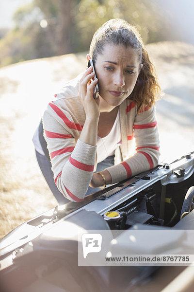 Frustrierte Frau spricht am Handy und schaut auf den Motor des Autos