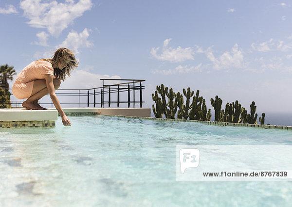 Frau taucht mit der Hand ins Schwimmbad
