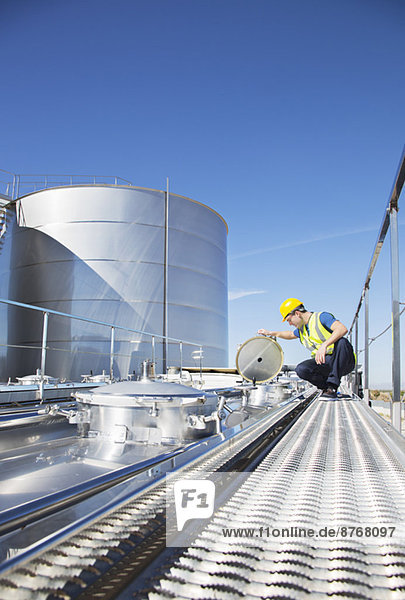 Arbeiter auf Plattform über Edelstahl-Milchtankwagen