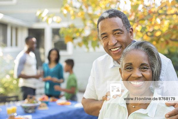 Porträt eines lächelnden Seniorenpaares beim Grillen
