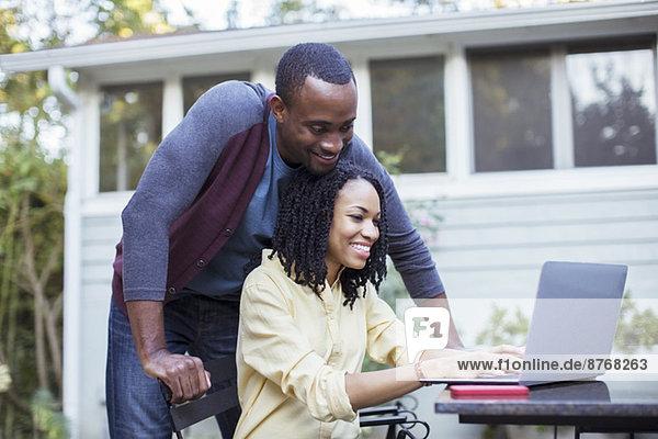Paar mit Laptop am Terrassentisch