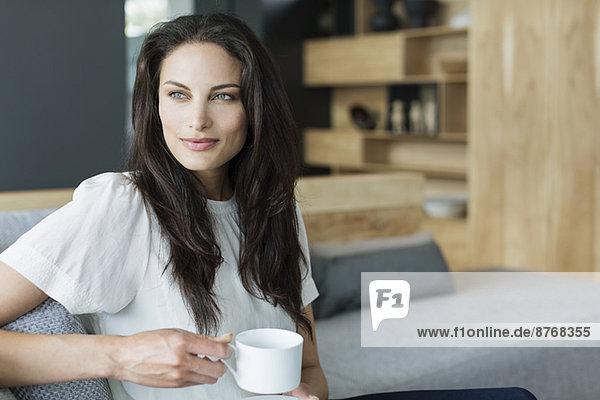 Frau trinkt Kaffee im Wohnzimmer