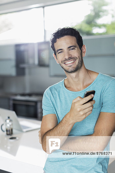 Porträt eines lächelnden Mannes mit Handy in der Küche