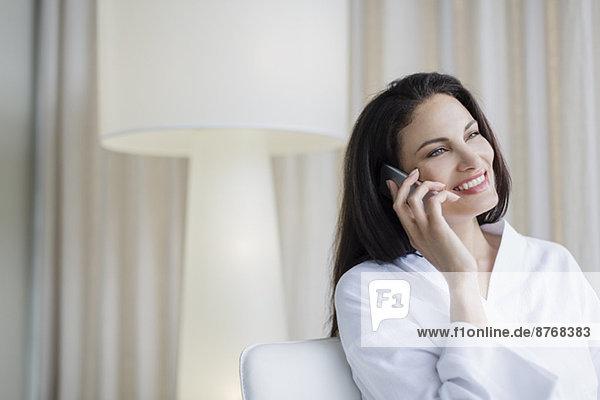 Lächelnde Frau im Bademantel spricht zu Hause am Handy