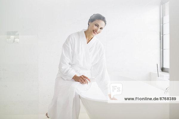 Porträt der lächelnden Frau im Bademantel beim Vorbereiten des Bades