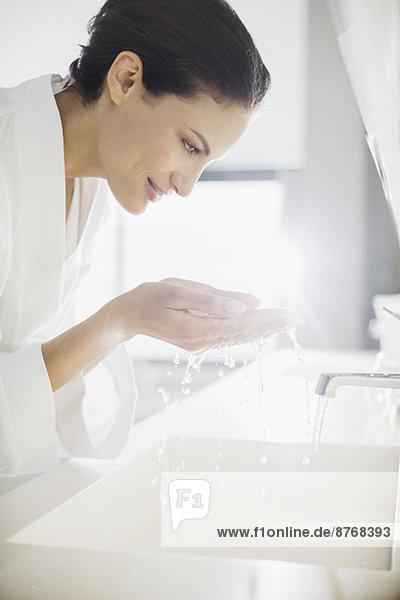 Frau im Bademantel spritzt Wasser ins Gesicht