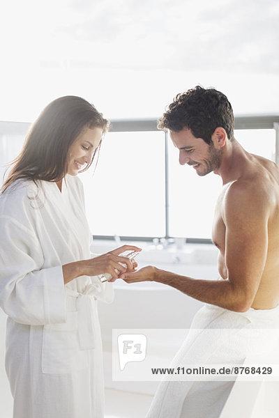 Frau spendet Feuchtigkeitscreme in der Hand des Mannes