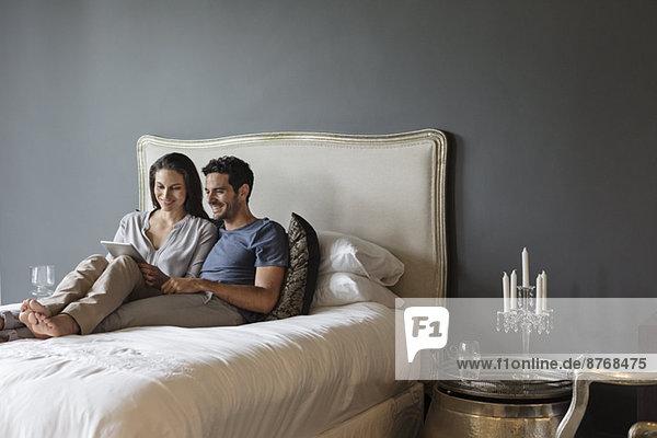Paar mit digitalem Tablett im Schlafzimmer