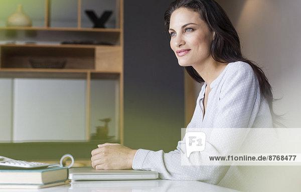 Selbstbewusste Frau am Tisch sitzend