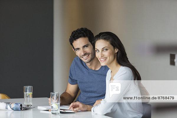 Porträt eines lächelnden Paares  das Rechnungen am Tisch bezahlt