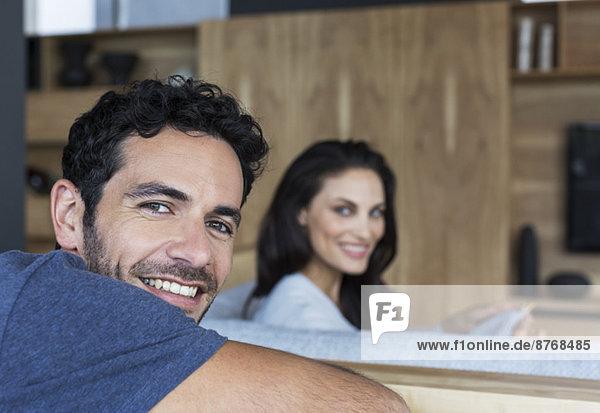 Porträt eines lächelnden Paares im Wohnzimmer