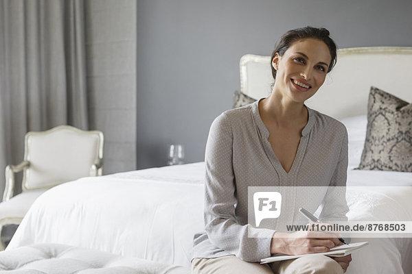 Glückliche Frau schreibt im Schlafzimmer