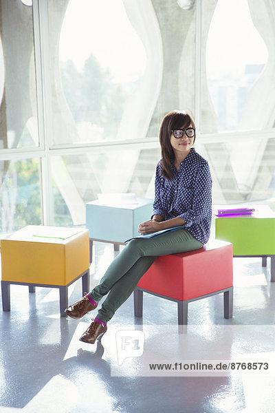 Kreative Geschäftsfrau wartet auf bunten Hocker