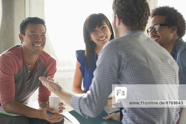 Glückliche  kreative Geschäftsleute in der Sitzung