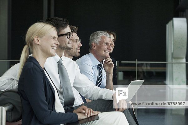 Group of smiling businesspeople with laptop