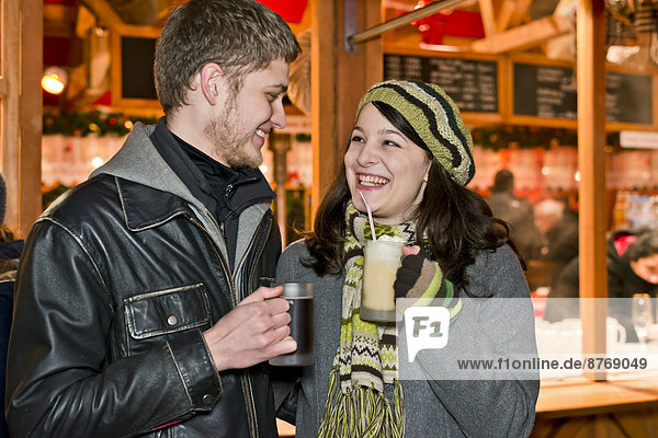 Germany  Berlin  happy young couple with hot beverages at Christmas market