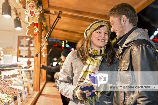 Deutschland  Berlin  junges Paar beim Kauf von gebrannten Mandeln auf dem Weihnachtsmarkt