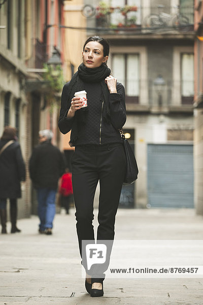 Spain  Catalunya  Barcelona  young black dressed businesswoman with coffee to go in front of a street