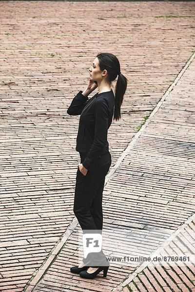 Spanien  Katalonien  Barcelona  junge schwarz gekleidete Geschäftsfrau telefoniert auf dem Platz