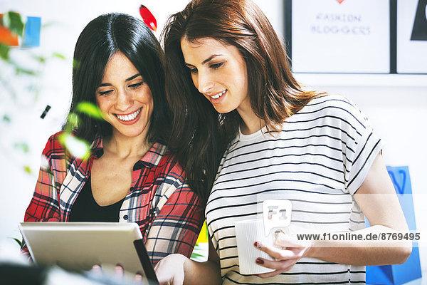 Zwei Mode-Bloggerinnen mit digitalem Tablett im Büro