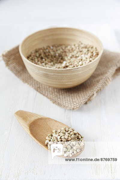 Bowl and wooden shovel of buckwheat grains on white wooden table