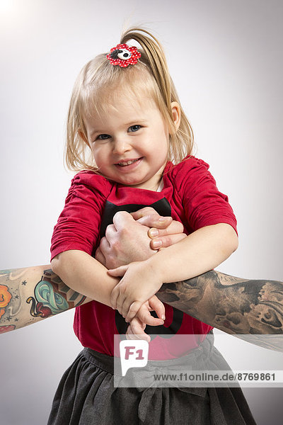 Girl holding tattooed arms