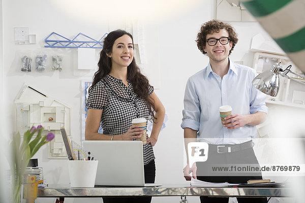 Porträt zweier junger lächelnder Architekten mit Pappbechern