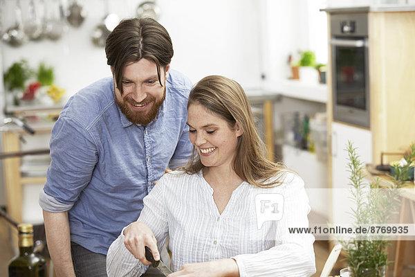 Glückliches Paar beim Zubereiten von Speisen in der Küche