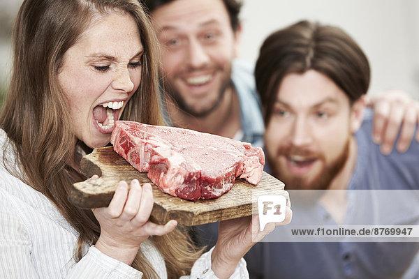 Glückliche junge Frau  die vorgibt  in rohes Steak zu beißen.
