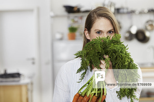 Young woman holding bunch of carrots in kitchen