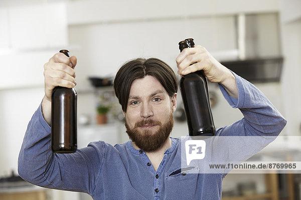 Mann in der Küche mit zwei Flaschen Bier