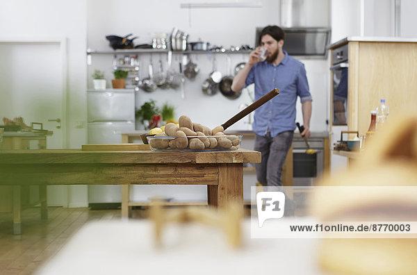 Mann in der Küche trinkt aus Glas