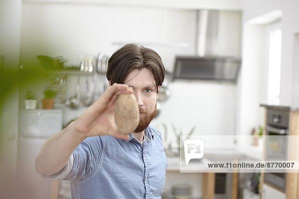 Mann in der Küche hält Kartoffel