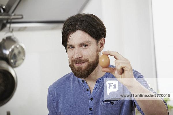 Mann in der Küche mit Ei